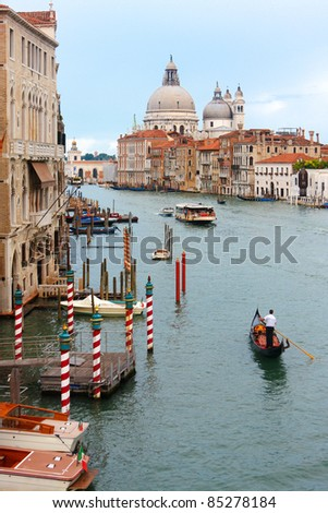 A gondola plows the Grand Canal with the Santa Maria Della Salute church in the background