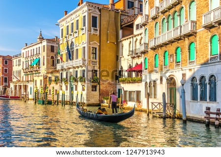 A gondolier in his gondola in the Grand Canal of Venice in front of old palaces #1247913943