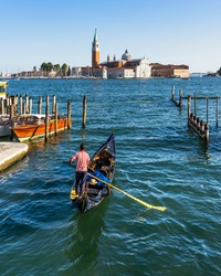A gondolier in Venice sailing under the Church of San Giorgio Maggiore at sunset, Italy