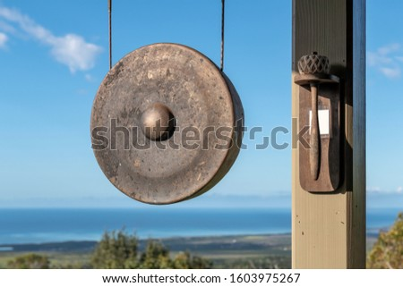 A gong hangs outdoors next to a mallet mounted on a post.  Background is an ocean view, lush vegetation and blue sky.