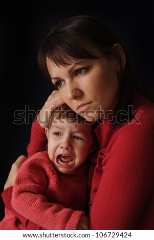 A good Caucasian mother with a sad crying daughter on a dark background