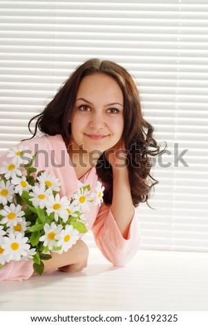 A good caucasian woman sitting at the table with a flower on a light background