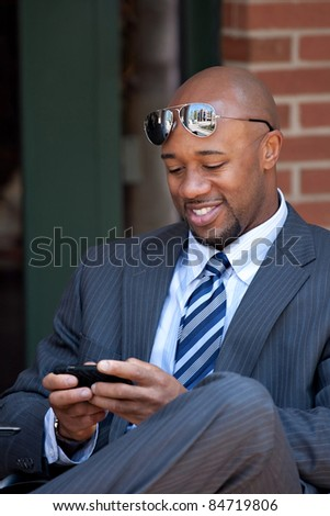 A good looking African American business man works on his smartphone with a smile on his face.