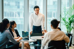 A good looking, confident and fit Asian Chinese man chairs a meeting with his team during the day in the office. He is professionally dressed in a shirt and pants and is gesturing as he speaks.