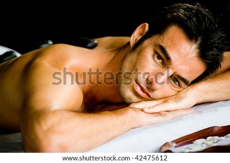 A good looking man lying on a massage bed with hot stones on his back