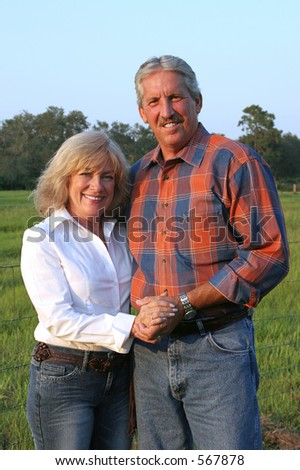 stock photo : A good-looking mature couple on a farm - vertical orientation