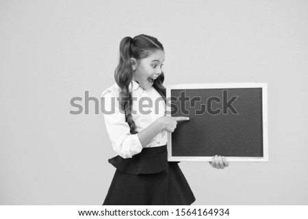 A good publicity for our school. Small kid pointing finger at blank blackboard with school publicity. Little child showing publicity event on tidy empty chalkboard. Publicity board, copy space.