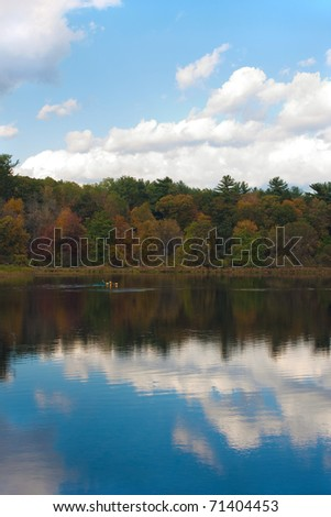 A gorgeous autumn scene with a lake and trees showing the bright colors of fall in New England. Kayakers enjoy the day in the distance.
