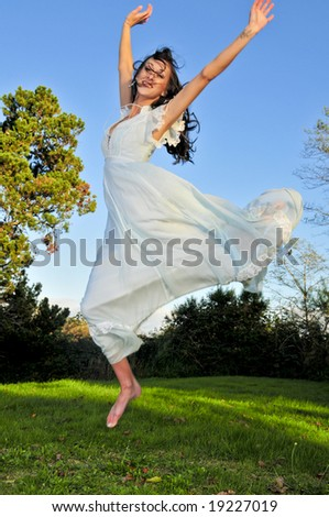 A gorgeous brunette jumping on a on a sunny day.