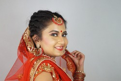 A gorgeous Indian bride with heavy makeup wearing traditional Indian bridal attire and posing