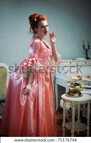 A gorgeous red-haired lady in a lavish ancient dress holding a cake