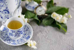 A gorgeous tea cup with green tea and jasmine blossoms.