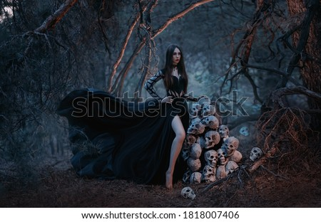 A gothic beautiful young woman in a black dress stands near a mountain of human skulls. Fashion model in the image of the goddess of death in a dark forest of trees. Silk fabric flies in the wind.