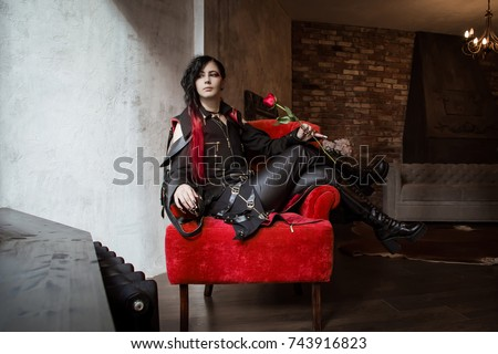 A gothic prince, a vampire, a man sits in a red armchair and holds a rose in his hands. A woman in a man's suit. Visual kei, aristocrat.