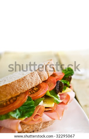 A gourmet sandwich of ham, cheese, lettuce, tomato and mayonnaise isolated on white.