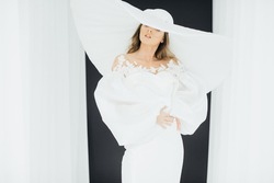 A graceful woman posing with a large wide-brimmed hat.