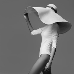 A graceful woman posing with a large wide-brimmed hat. Black and white image.