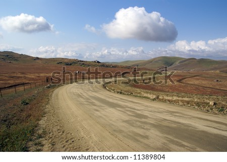 A graded dirt road snakes into the foothills, Sierra Nevada Mountains, California