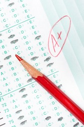 A graded test form with red scoring pencil indicates acheivement and success in education.