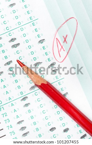 A graded test form with red scoring pencil indicates achievement and success in education.