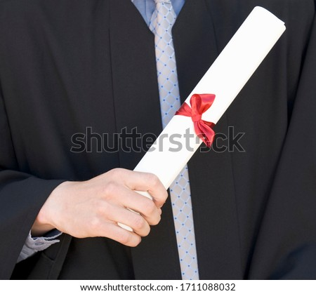 A graduate holding his diploma, close-up