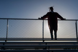 A graduating high school teenage boy wearing a cap and gown leans against a stadium fence and is silhouetted by the setting sun.