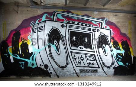 a graffiti artwork of a boom box ghettoblaster on a wall
