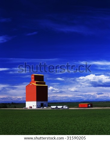 A grain truck pulls away from a grain elevator on the prairies.