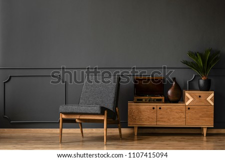 A gramophone on wooden cabinet and black chair in dark retro room interior