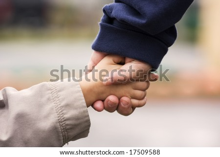 A grand-mother holding her grand-son's hand in hand