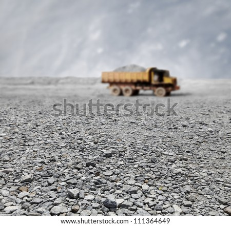 A granite quarry mine with a tipper lorry transporting stones in the horizon.