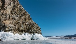 A granite rock, devoid of vegetation, against the background of a blue sky and a frozen lake. Deep cracks on the stones. On the base - ice splashes, icicles. Winter sunny day. Baikal