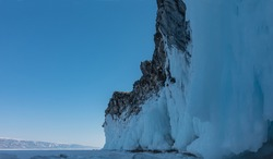 A granite rock, devoid of vegetation, rises above the frozen Lake Baikal. The base is covered with a thick layer of fancy icicles. In the distance, against the background of a blue sky, a mountain ran