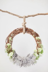 a grape cradle ring hanging on a rope on a stick, decorated with green flowers and leaves with a gray wool rug for shooting newborns and children up to a year, idea for a photo shoot