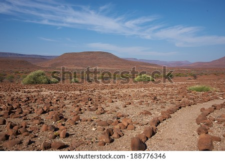 A gravel path marked by edging stones meanders through the arid landscape of northern Damaraland in Namibia