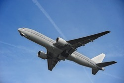 A gray Boeing 777 airplane taking off from an airport