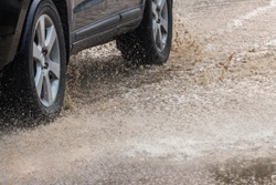 A gray car speeding through the sewage road splashing yellow water splash