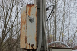a gray metal box in brown rust and with electric wires hanging on a concrete pole outside