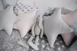 a gray pillows in the nursery on the bed