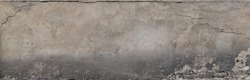 A gray plastered wall with a crumbling dirty texture