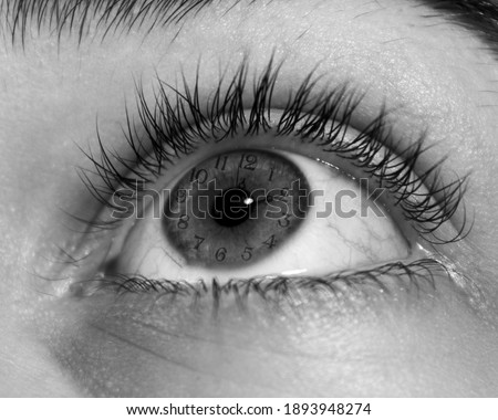 A grayscale closeup shot of a human open eye looking to the top