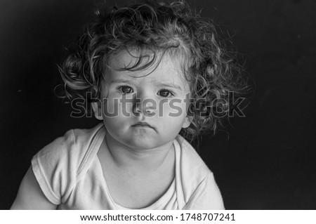A grayscale portrait of an adorable toddler with curly hair and serious facial expression
