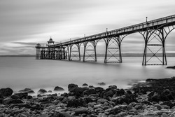 A grayscale shot of a bridge over a lake and stones on the bay on a cloudy da