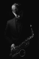 A grayscale shot of a cool and handsome guy holding his saxophone on a dark background