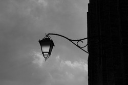A grayscale shot of a decorative street lamp against the cloudy sky