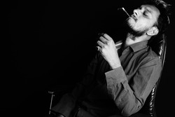 A grayscale shot of a handsome Asian male relaxing in the armchair with a cigarette