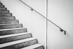 A grayscale shot of a staircase with a metallic handle