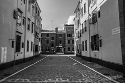 A grayscale shot of a street between two buildings in Venice, Italy