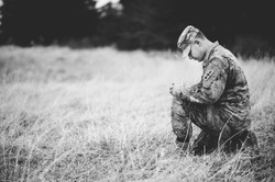 A grayscale shot of a young soldier praying while kneeling on a dry grass