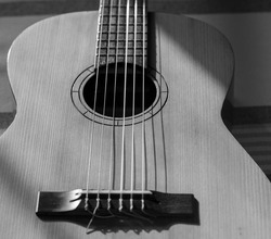 A grayscale shot of an acoustic guitar